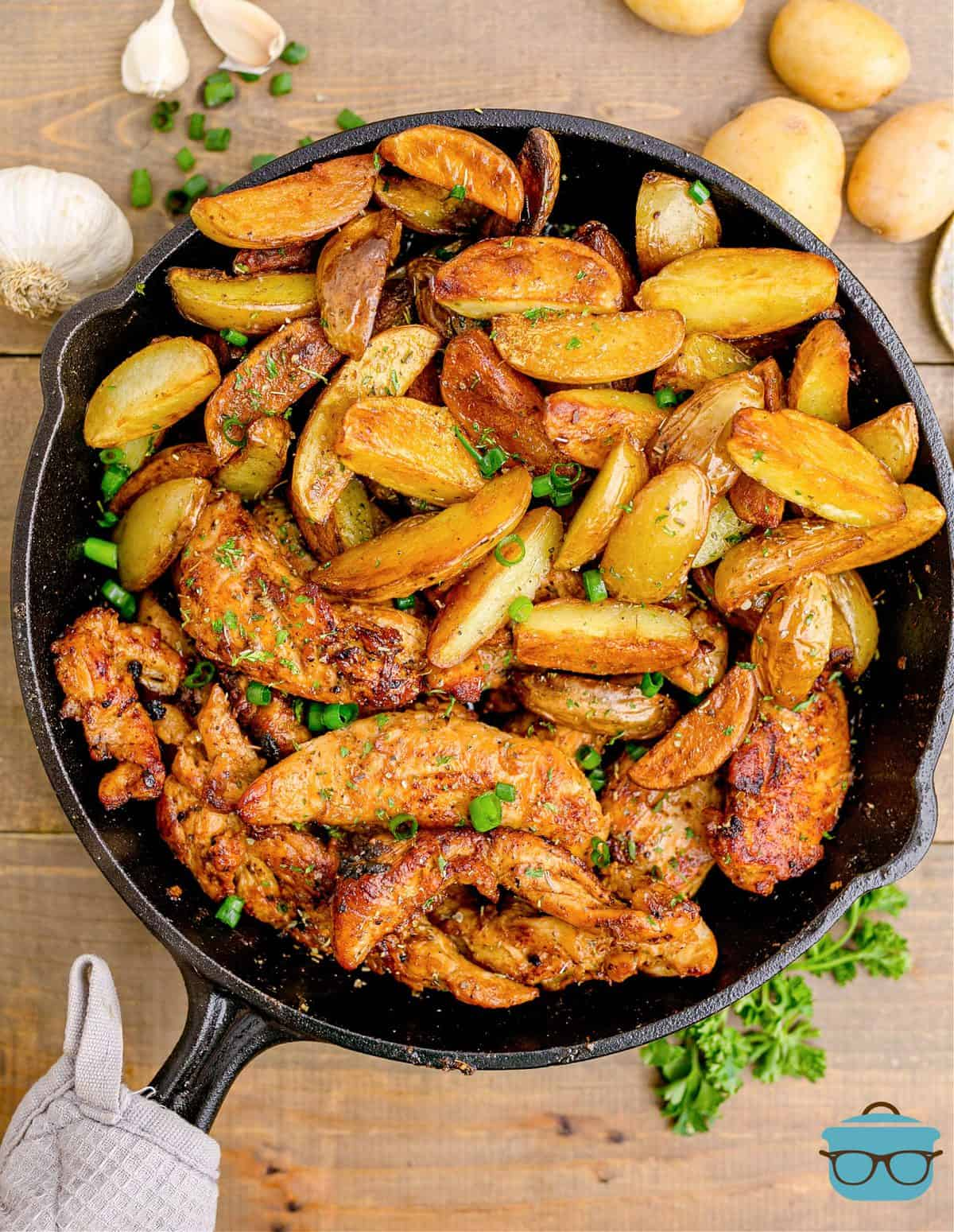 Chicken and Potatoes in skillet overhead with towel around handle of skillet.