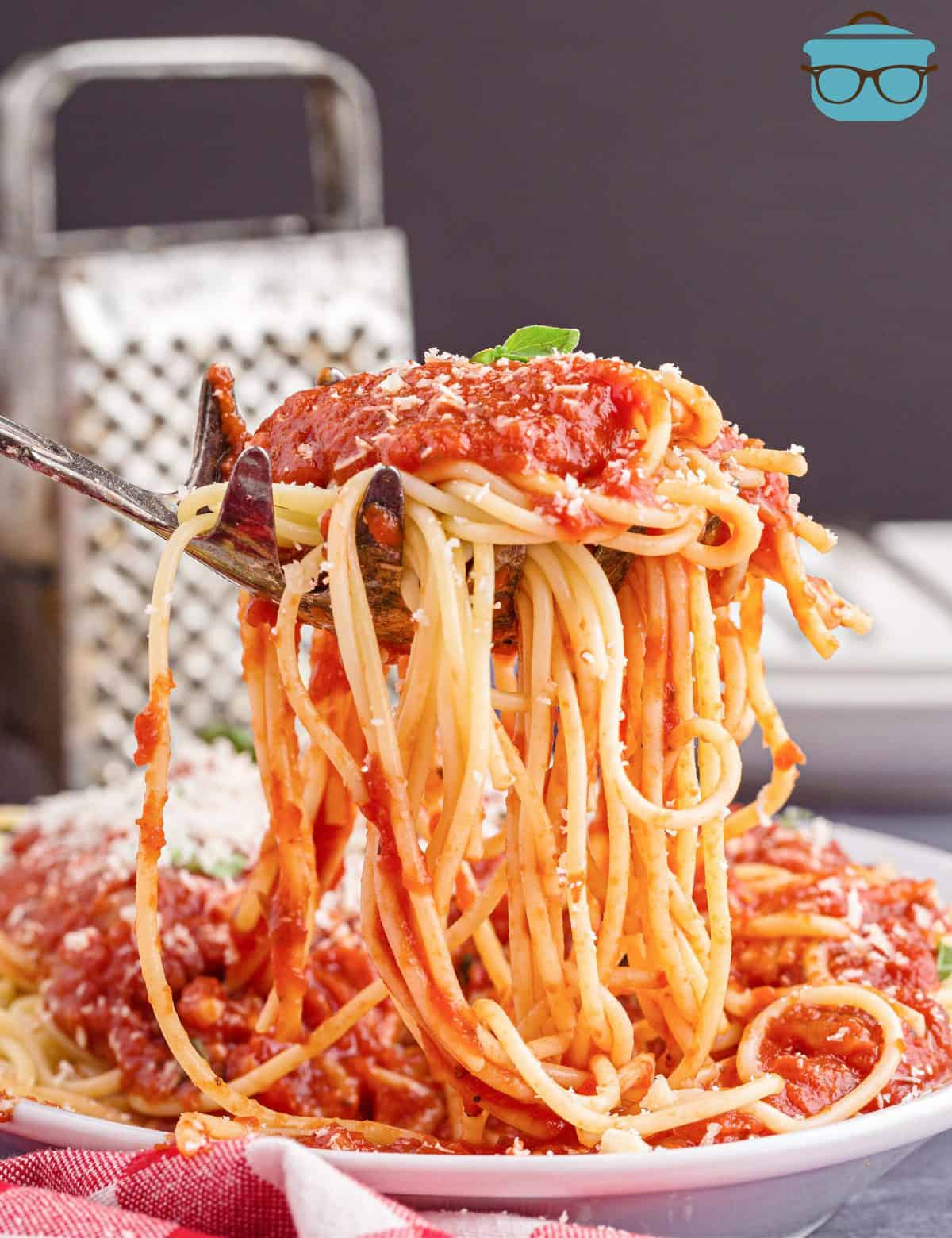 Large spoon holding up spaghetti off plate with Homemade Marinara Sauce on it.