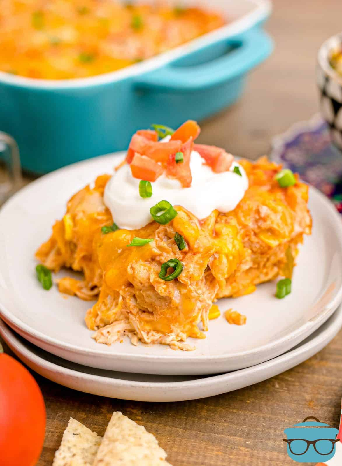 Plate of Lazy Chicken Enchiladas topped with sour cream, green onions and tomatoes.