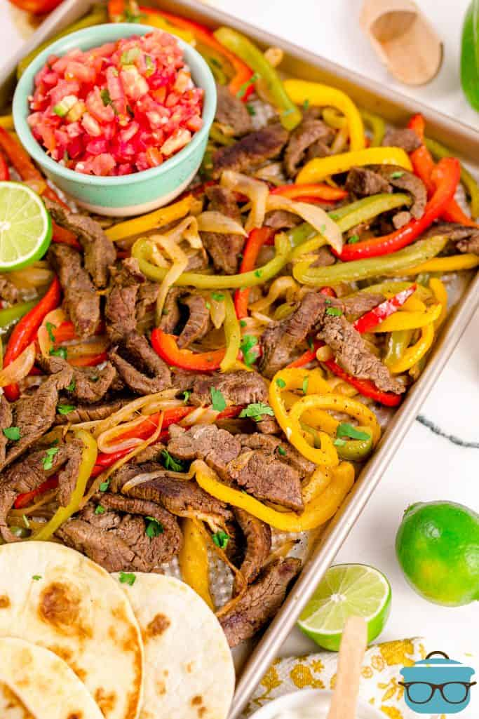Finished Sheet Pan Beef Fajitas on pan with toppings and tortillas.