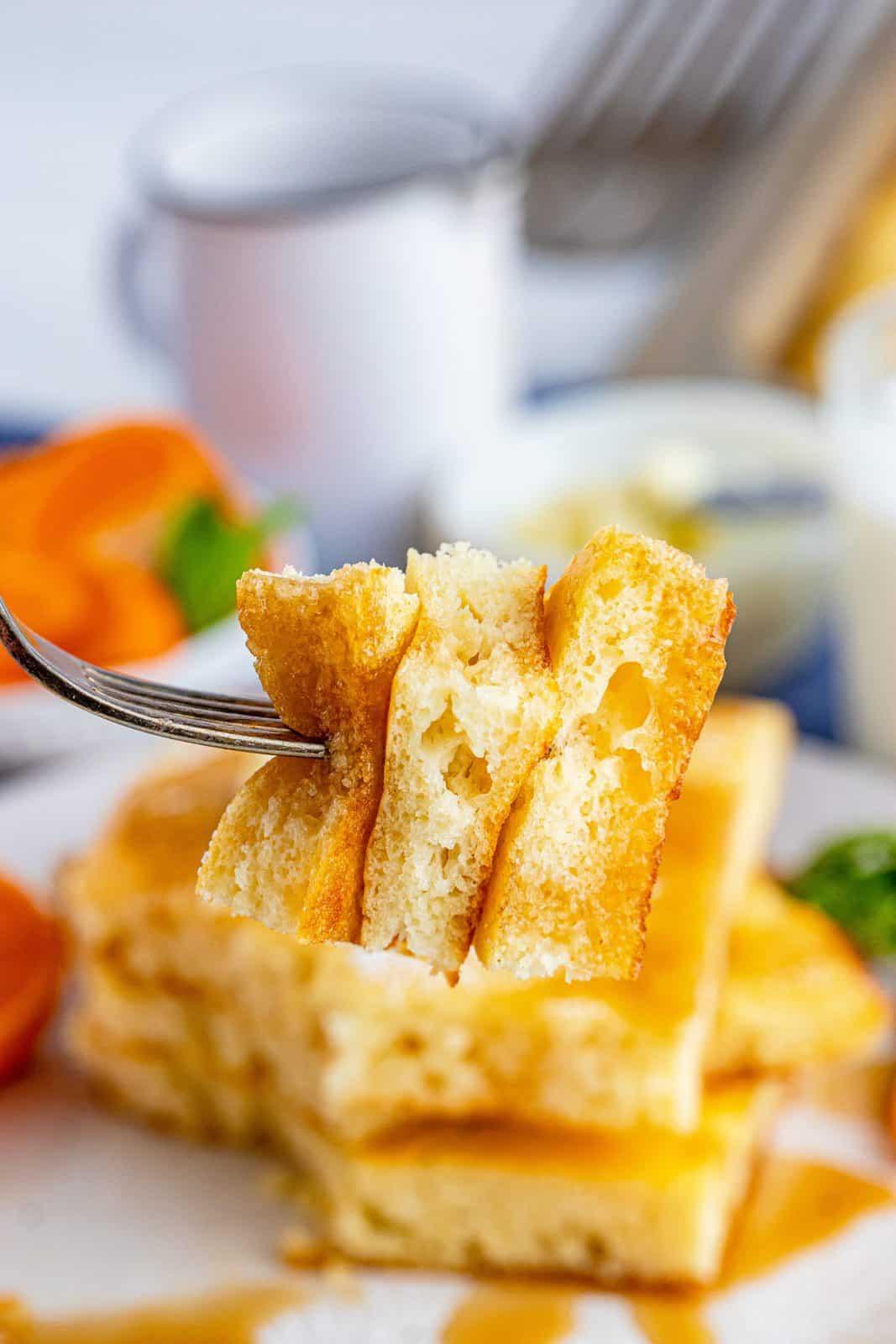 Fork holding bites of pancakes on fork.