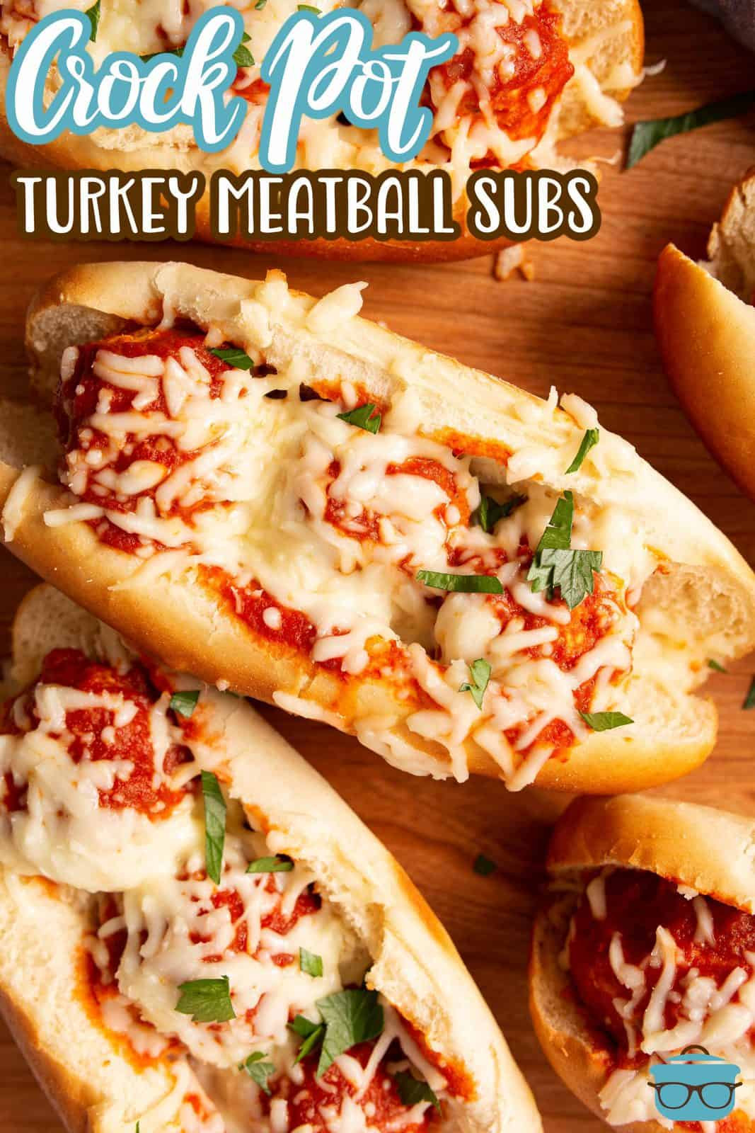 Pinterest image overhead of finished Crock Pot Turkey Meatball Subs with melted cheese and parsley.