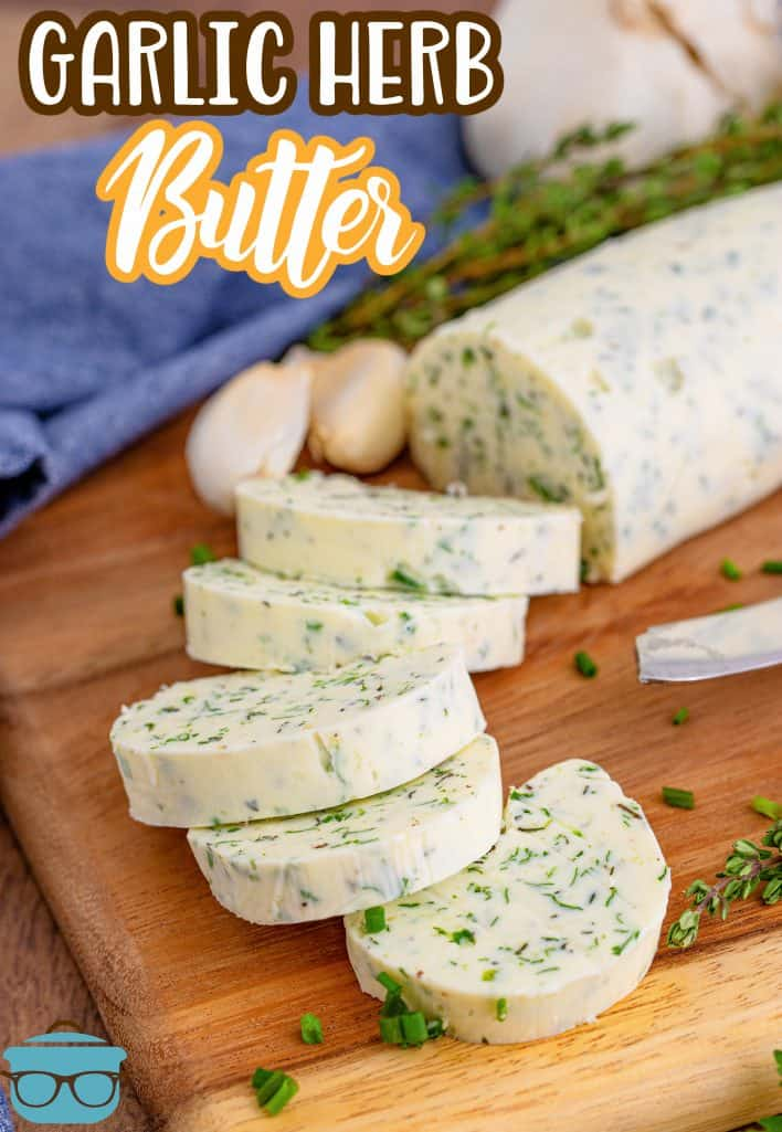 Sliced Garlic Herb Butter in rounds on wooden board with herbs next to butter Pinterest image.