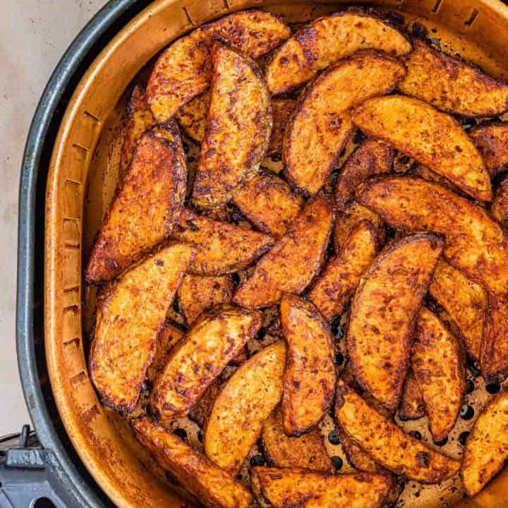 Square image of Air Fryer Potato Wedges in basket.