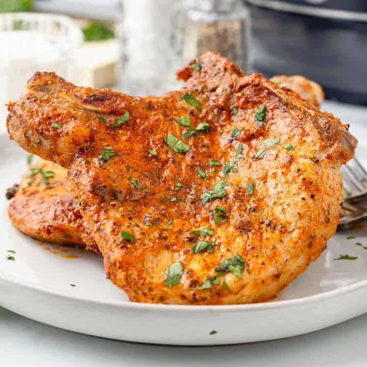 Square image of close up Air Fryer Ranch Pork Chops on white plate.