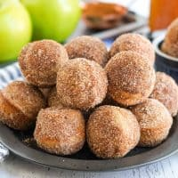 Square image of Apple Cider Donut Holes on black plate stacked.