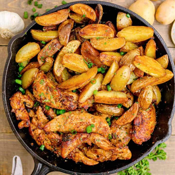 Square image of Garlic Butter Chicken and Potatoes in cast iron skillet garnished with parsley.