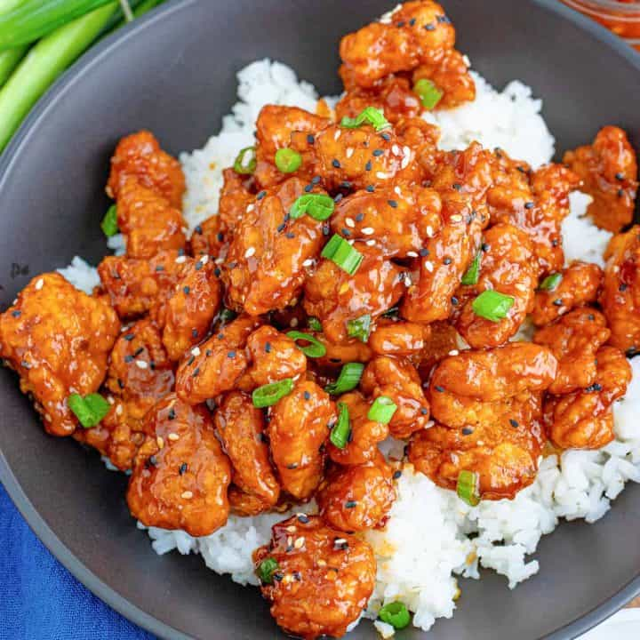 Square image of Easy General Tso's Chicken over white rice with sesame seeds and scallions.