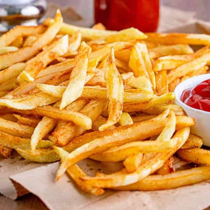 thumbnail photo of fully cooked homemade French Fries on a brown paper towel and ketchup in the background