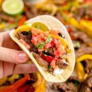 Squarer image of hand holding fajitas in a tortilla.