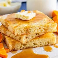 Square photo of three stacked Sheet Pan Pancakes with butter and syrup.