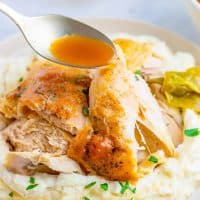 Square image of spoon dripping gravy over chicken on plate.