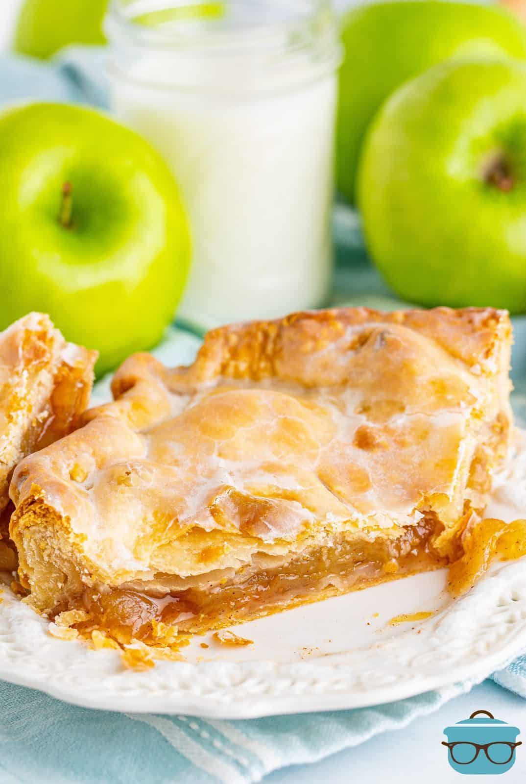 Slice of Apple Slab Pie on white plate with bite taken out showing inside.