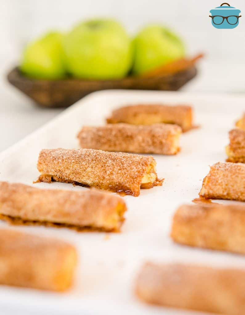 Finished Baked Apple Pie Rollups on white board with apples in background.
