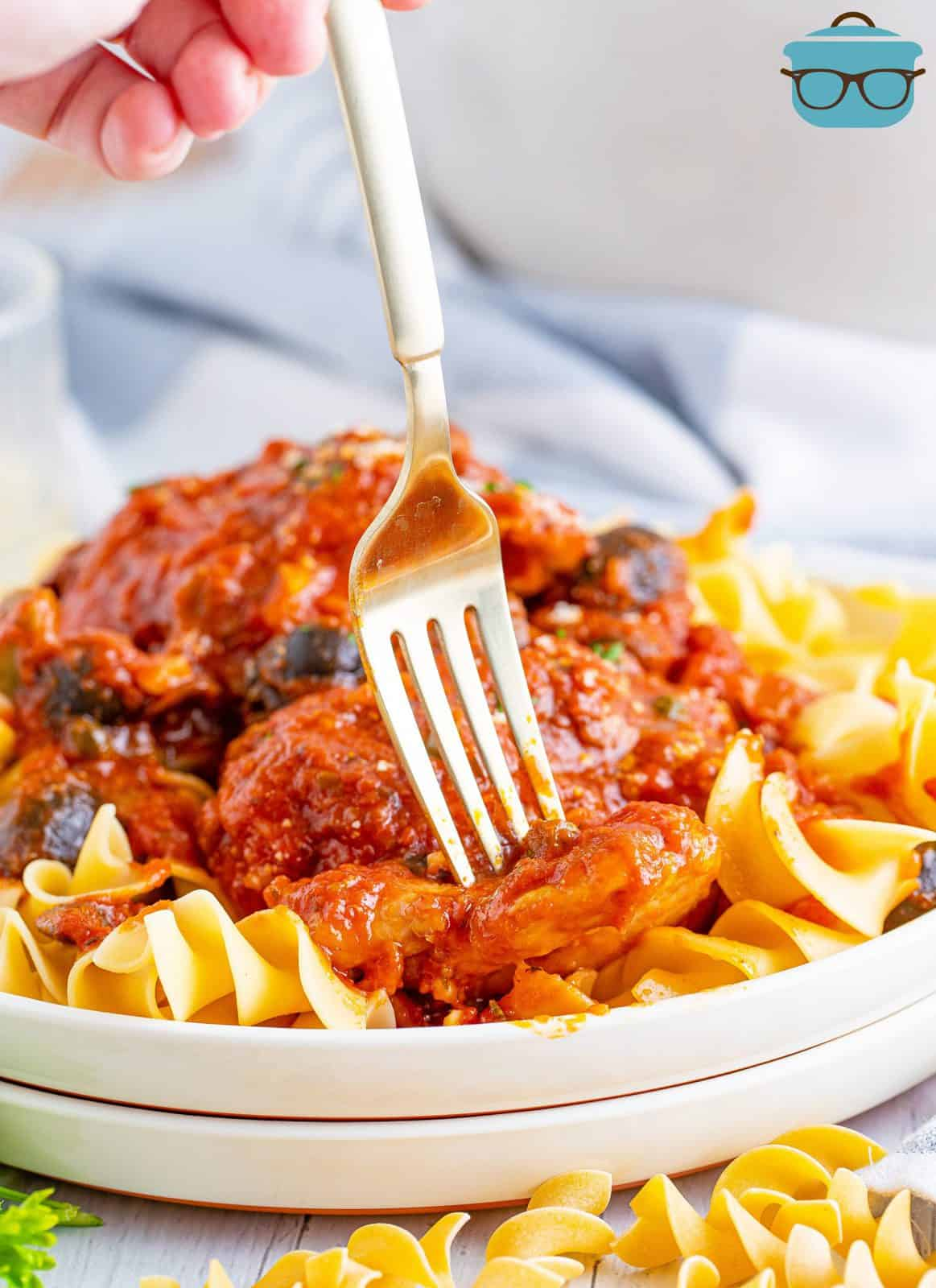 Fork going into piece of Chicken Cacciatore on plate over noodles.