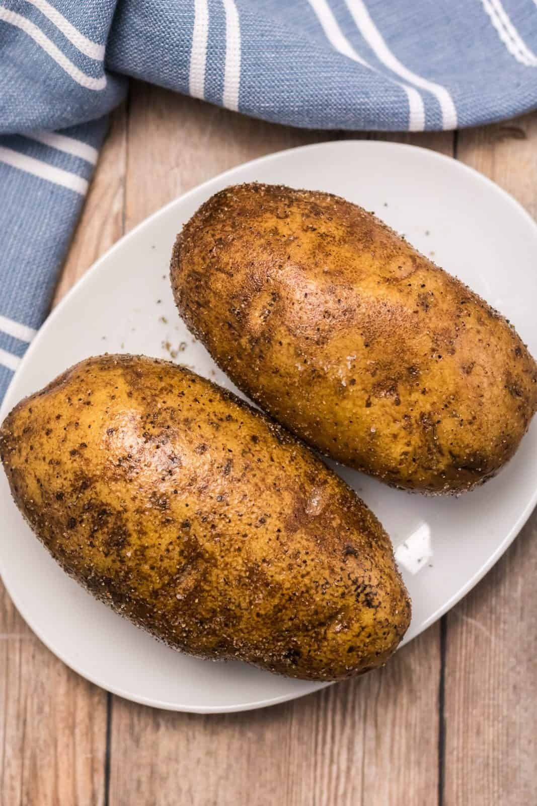 Two potatoes rubbed with oil, salt and pepper.