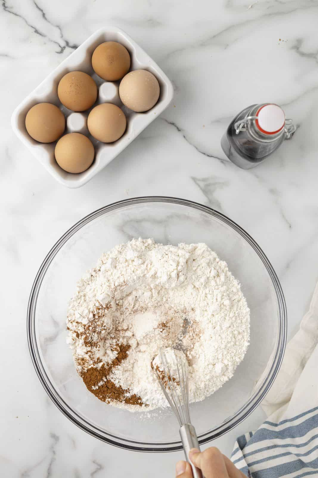 Flour, baking powder, cinnamon, salt, and nutmeg being whisked together in bowl.