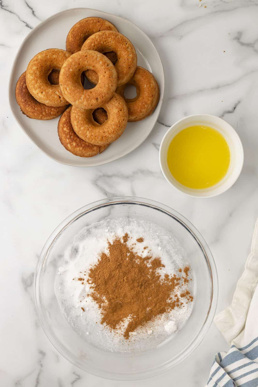 Cinnamon and sugar in bowl with butter and plate of donuts.