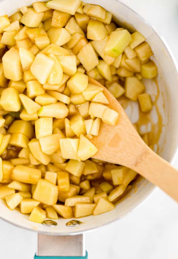 Apples added to mixture in sauce pan being stirred around.
