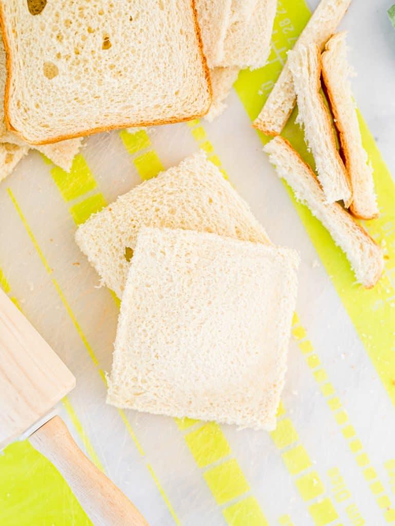 Sandwich bread with crusts cut off rolled flat.