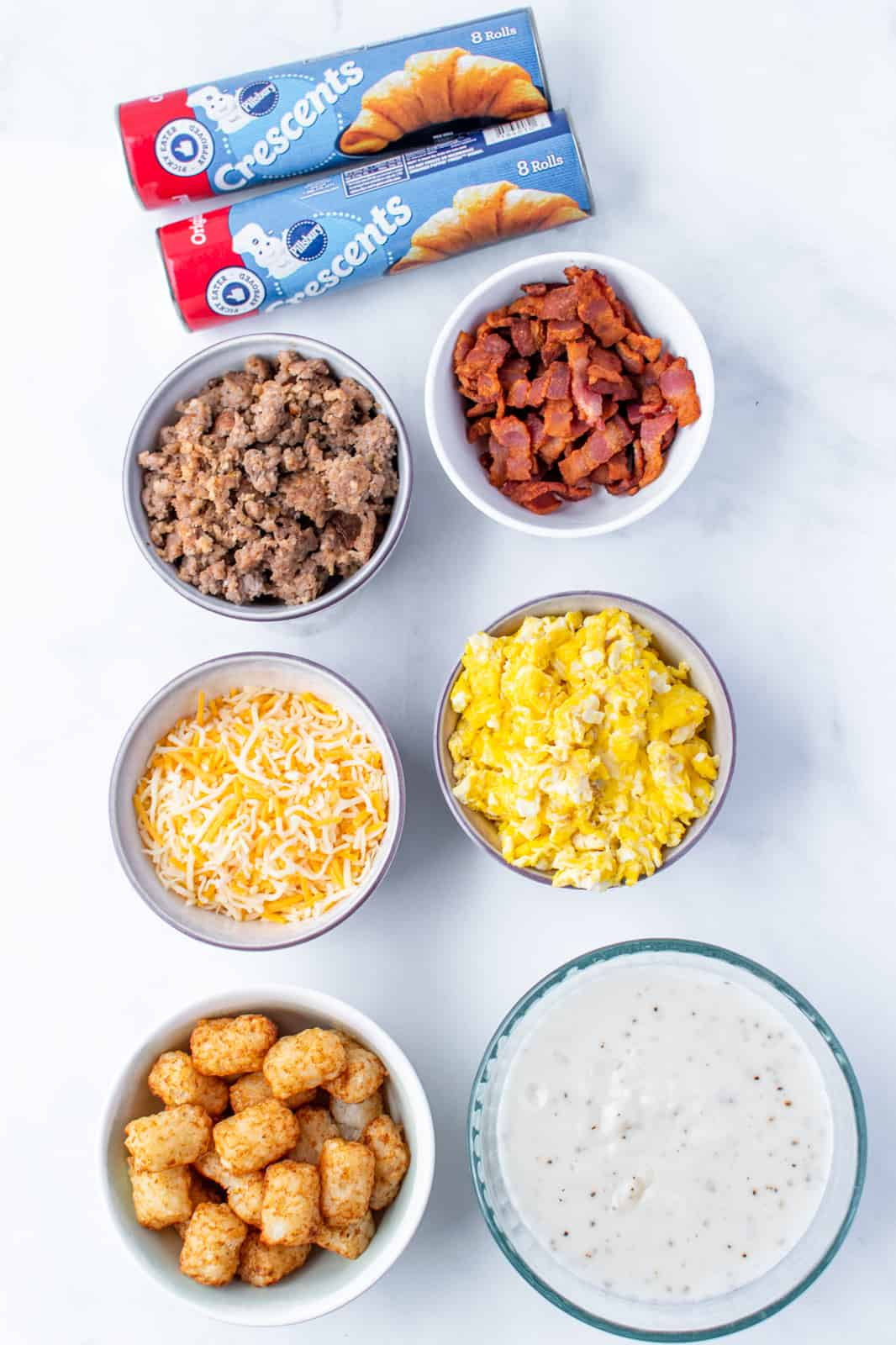 Ingredients needed: crescent rolls, tater tots, scrambled eggs, breakfast sausage, bacon, colby jack cheese, butter, poppy seeds and breakfast gravy.