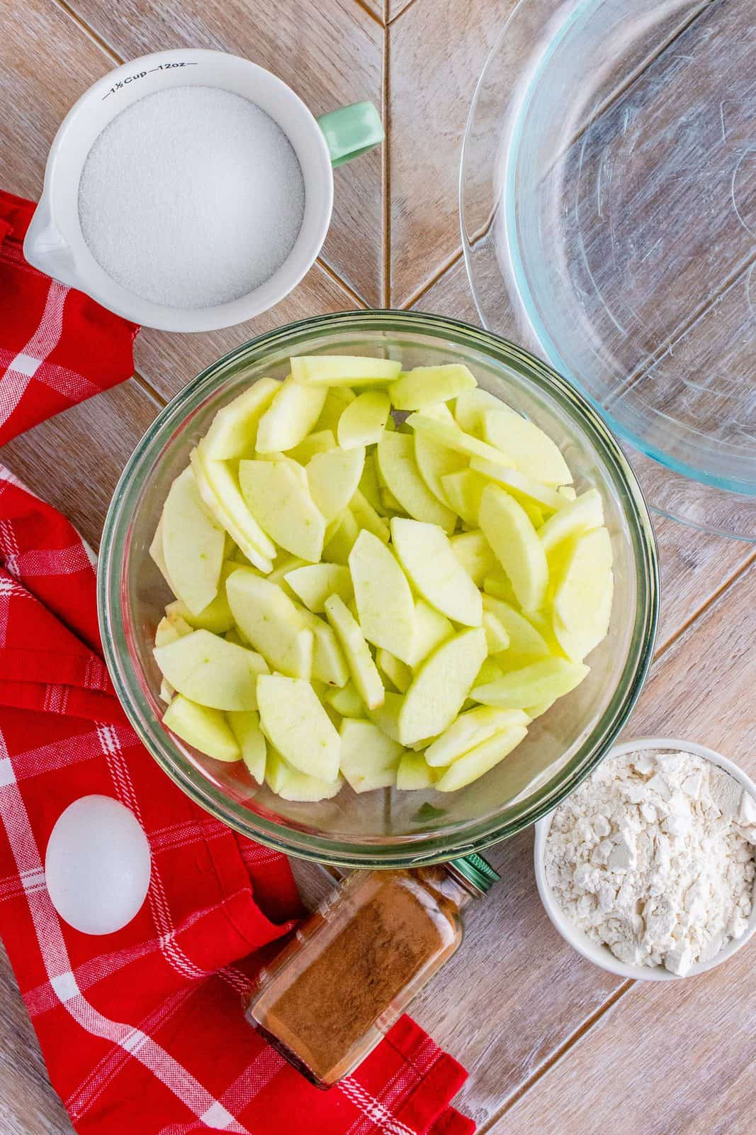 Sliced apples added to clear bowl.