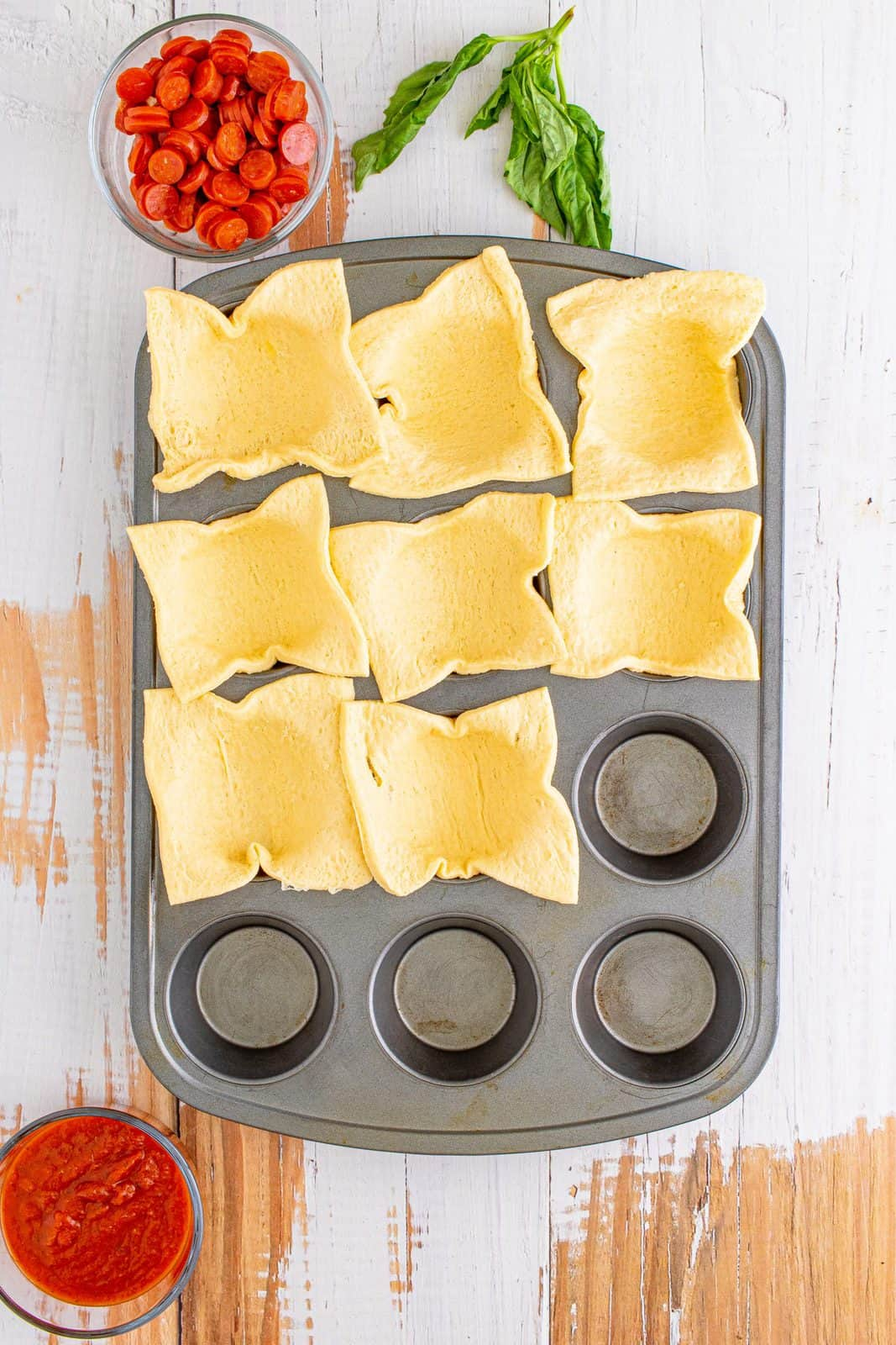Crescent dough sheet cut into 8 sections and placed into prepared muffin tin.