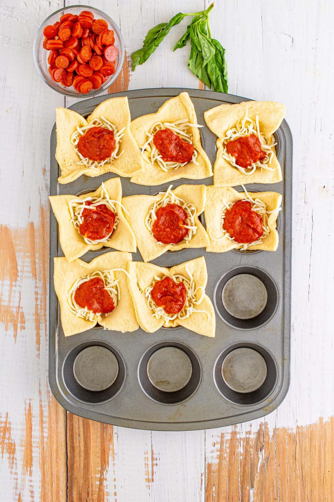 Pizza sauce added on top of cheese in muffin tin.