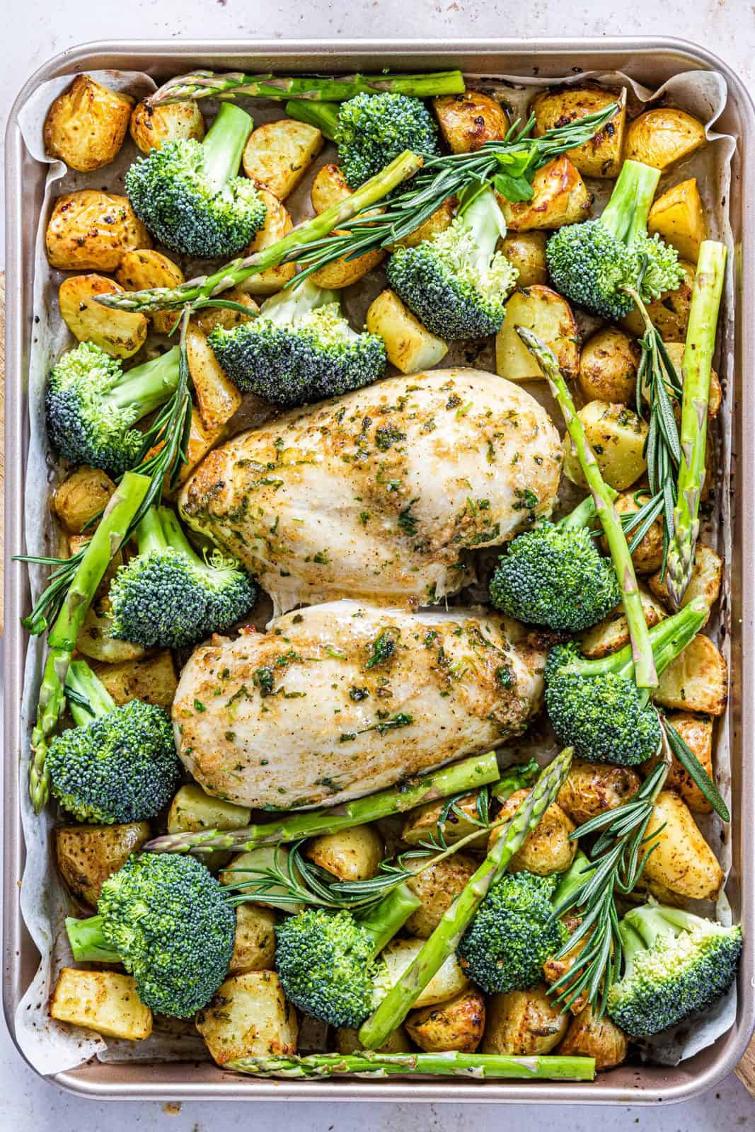 Asparagus, broccoli and rosemary added to pan with chicken and potatoes.