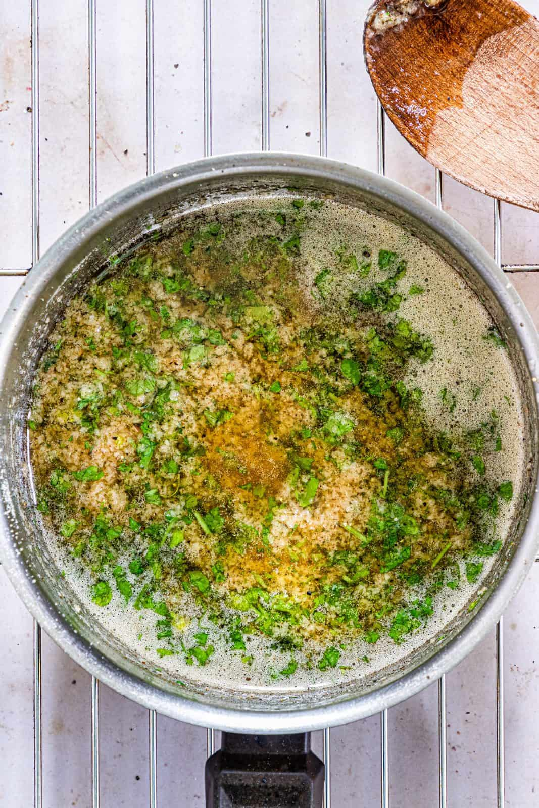 Garlic, parsley, salt and black pepper added to browned butter in pan.
