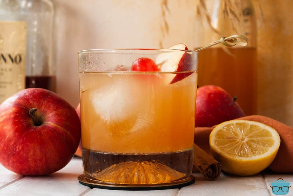 Close up of glass of Apple Cider Amaretto Sour in glass next to apples and lemons