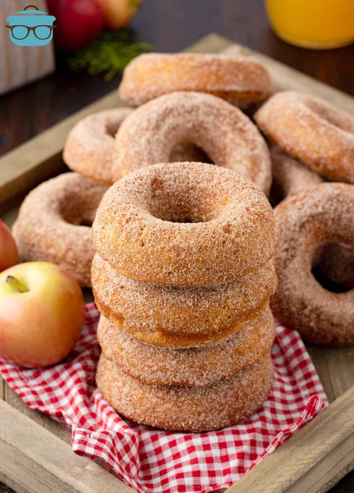 Four stacked Baked Apple Cider Donuts on tray with apple and more donuts behind it.