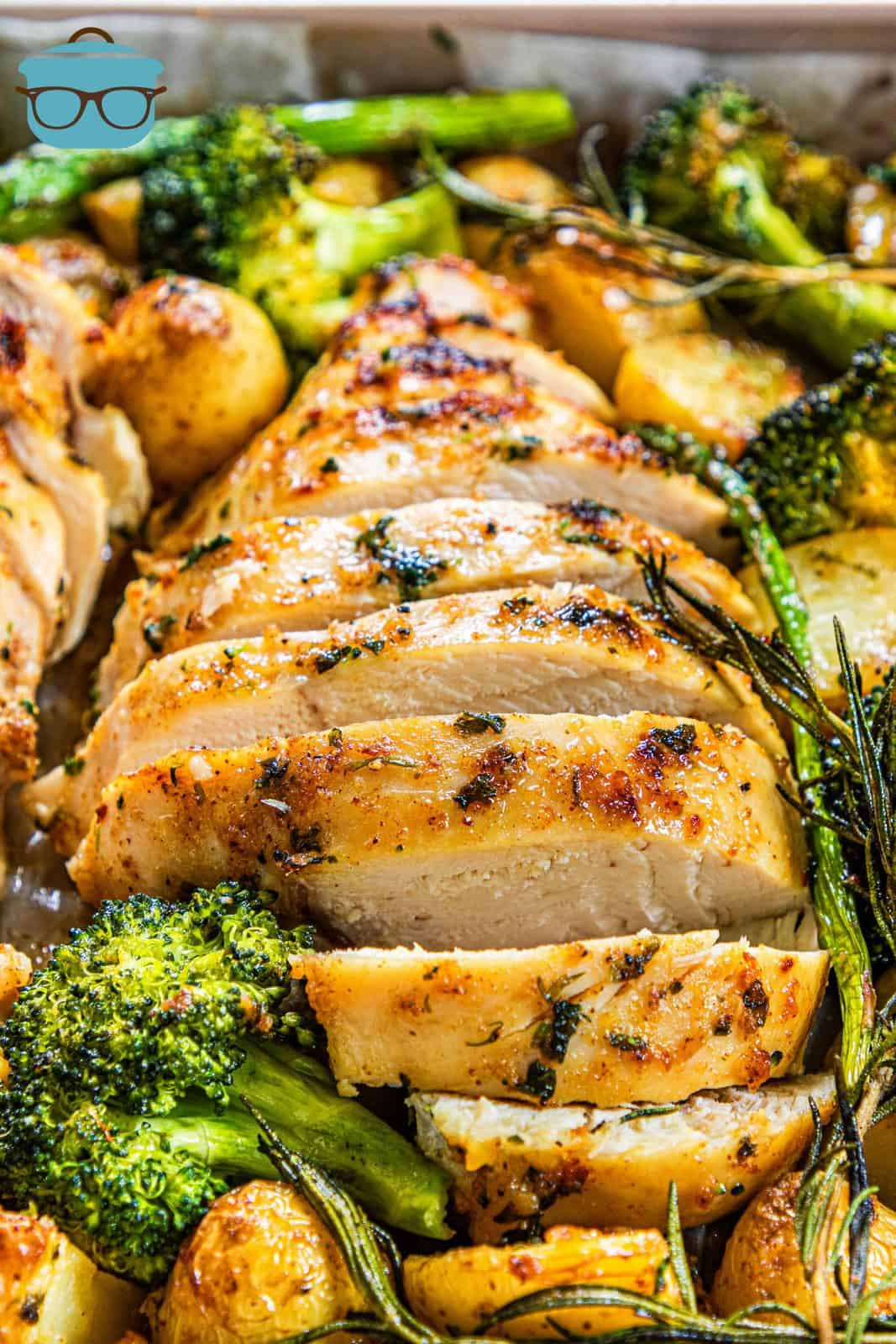 Close up of sliced chicken with vegetables on sheet pan.