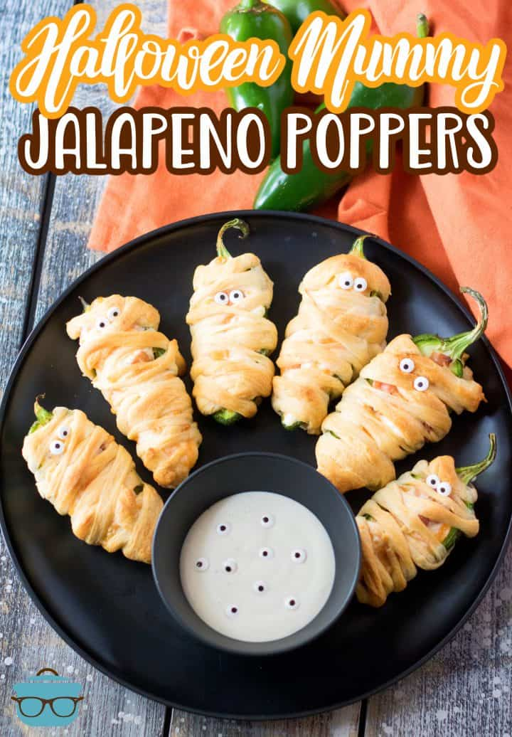 Pinterest image of finished Halloween Mummy Jalapeno Poppers on black plate with dipping sauce.