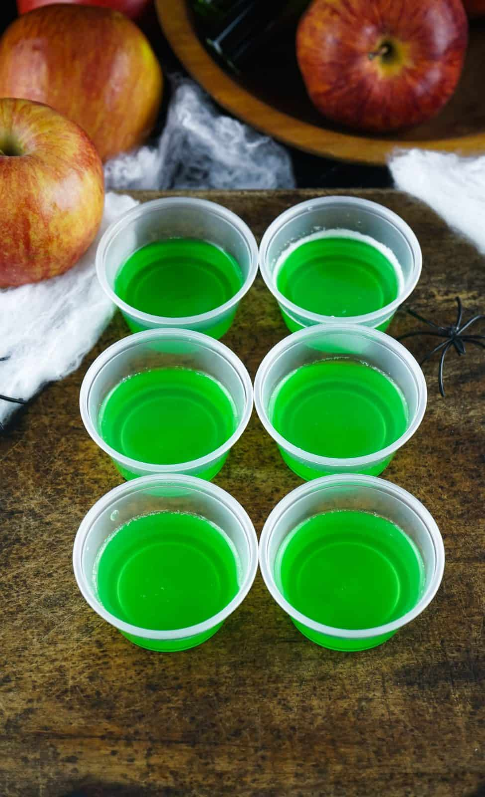 Small plastic cups with jell-o mixture poured halfway in cups.