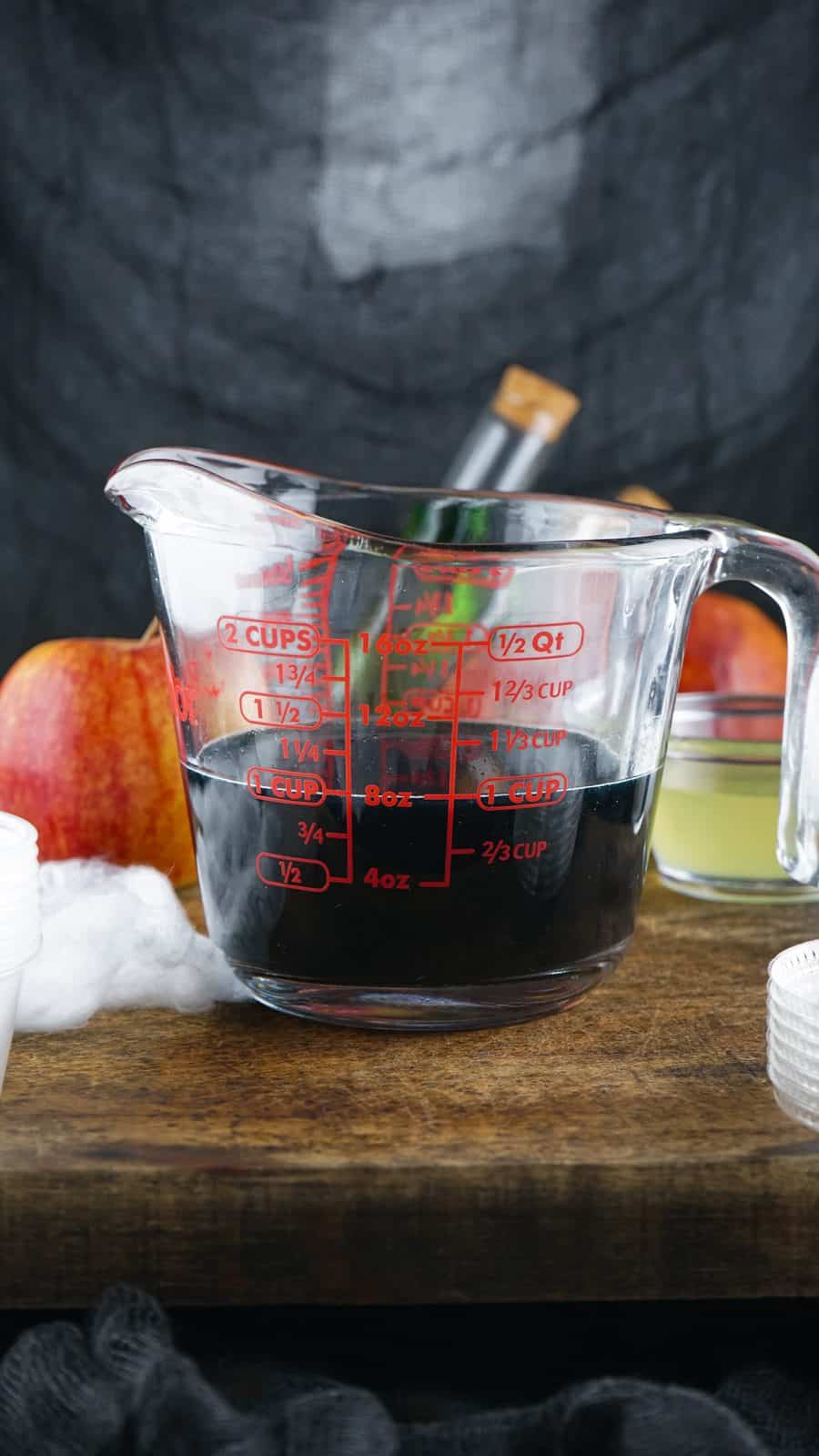 Remaining jell-o mixture with black food coloring added in measuring cup.