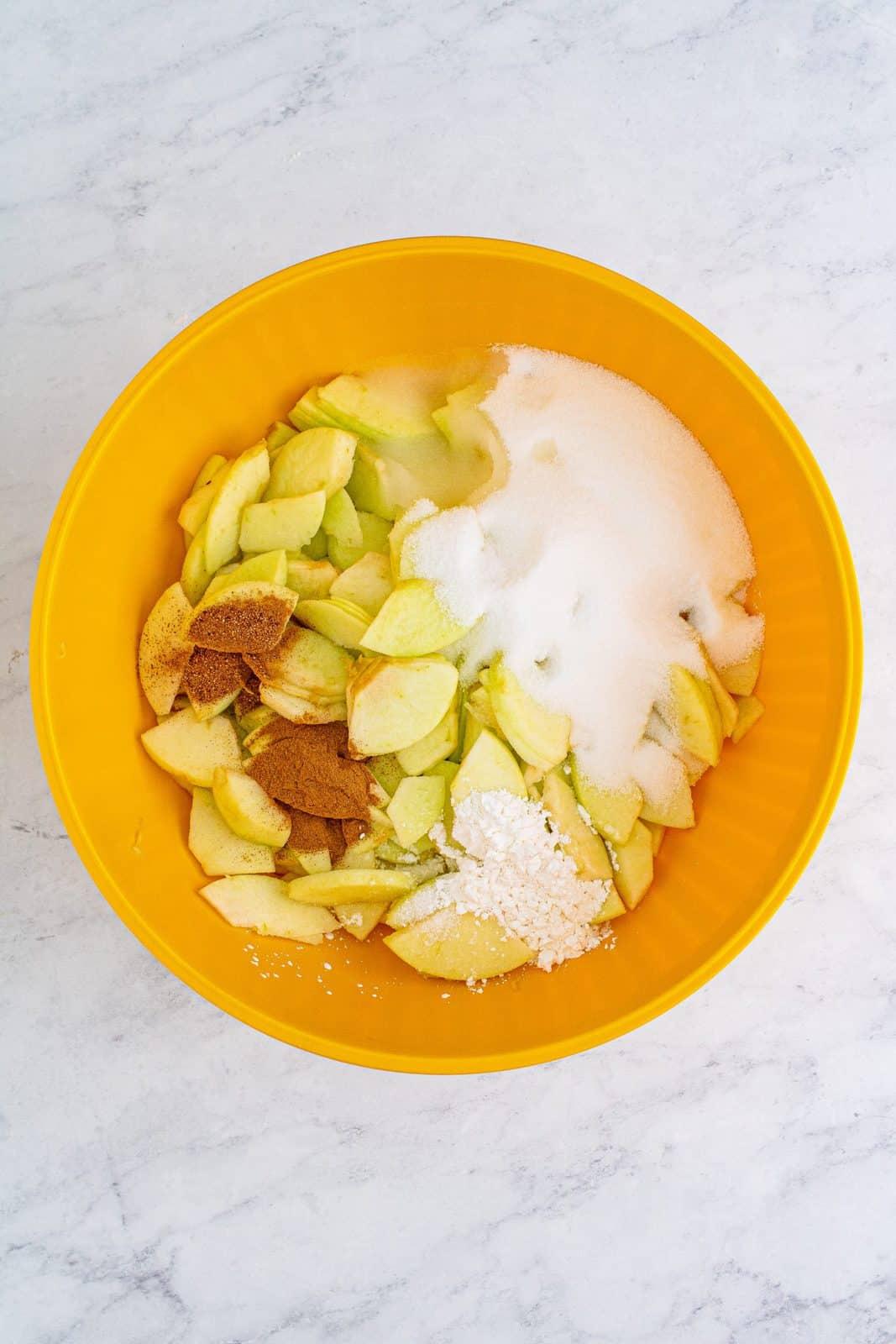Apples, sugar, cornstarch, lemon juice, cinnamon, nutmeg, and salt added to bowl.