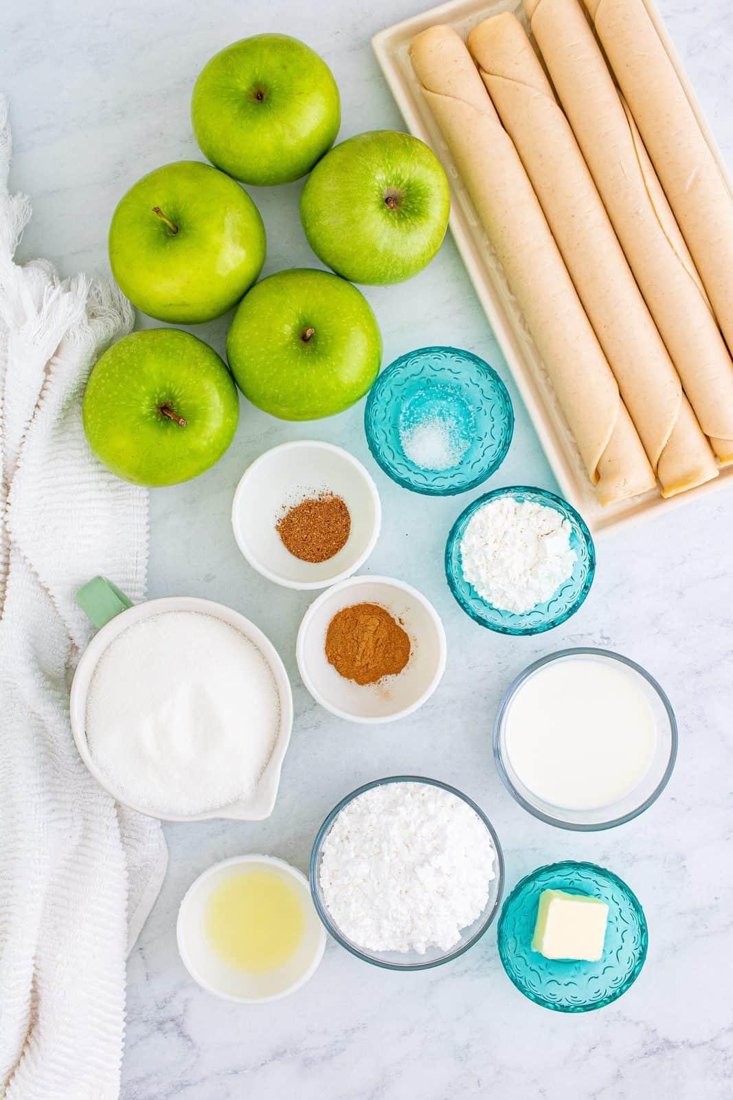 Ingredients needed: refrigerator pie crusts, apples, granulated sugar, cornstarch, lemon juice, ground cinnamon, ground nutmeg, salt, whole milk, unsalted butter and powdered sugar.