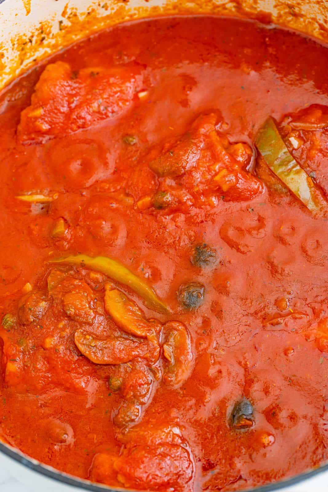 Sauce covering chicken as it simmers.