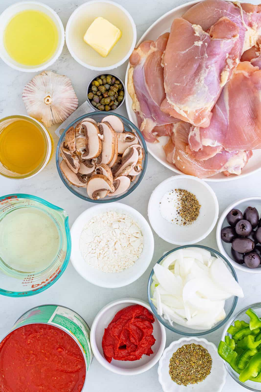 Ingredients needed: chicken thighs, kosher salt, pepper, all-purpose flour, vegetable oil, unsalted butter, onion, green bell pepper, mushrooms, garlic, dry white wine, crushed tomatoes with basil, chicken stock, tomato paste, ½ cup black pitted olives, capers, Italian seasoning, parsley and parmesan cheese.