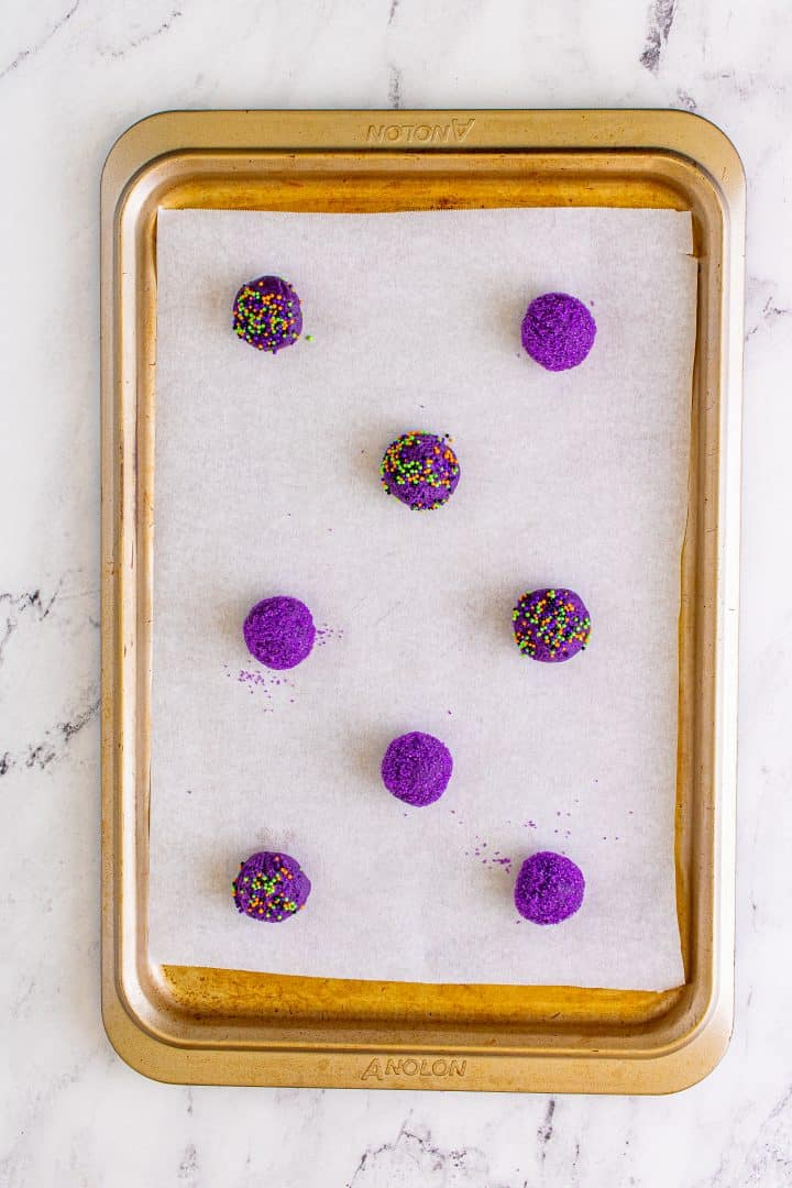 Cookie dough balls placed on lined baking sheet ready for baking.