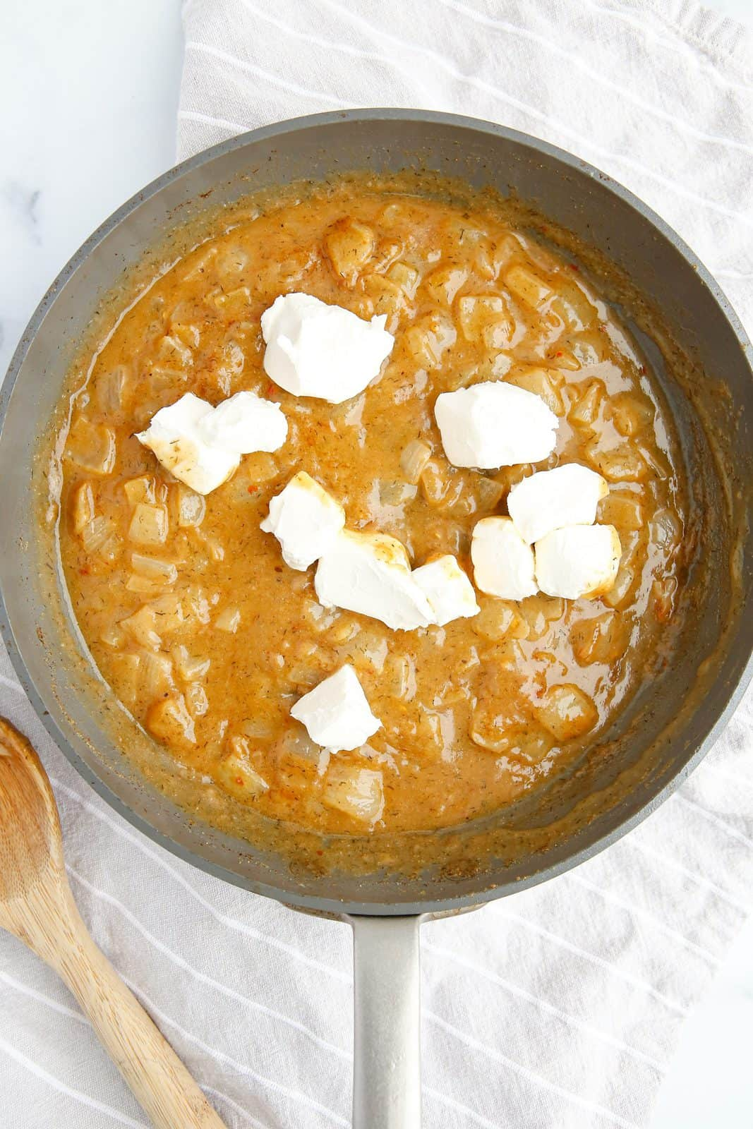 Melted butter, flour, onion, spices and broth mixture with cream cheese chunks and milk added.