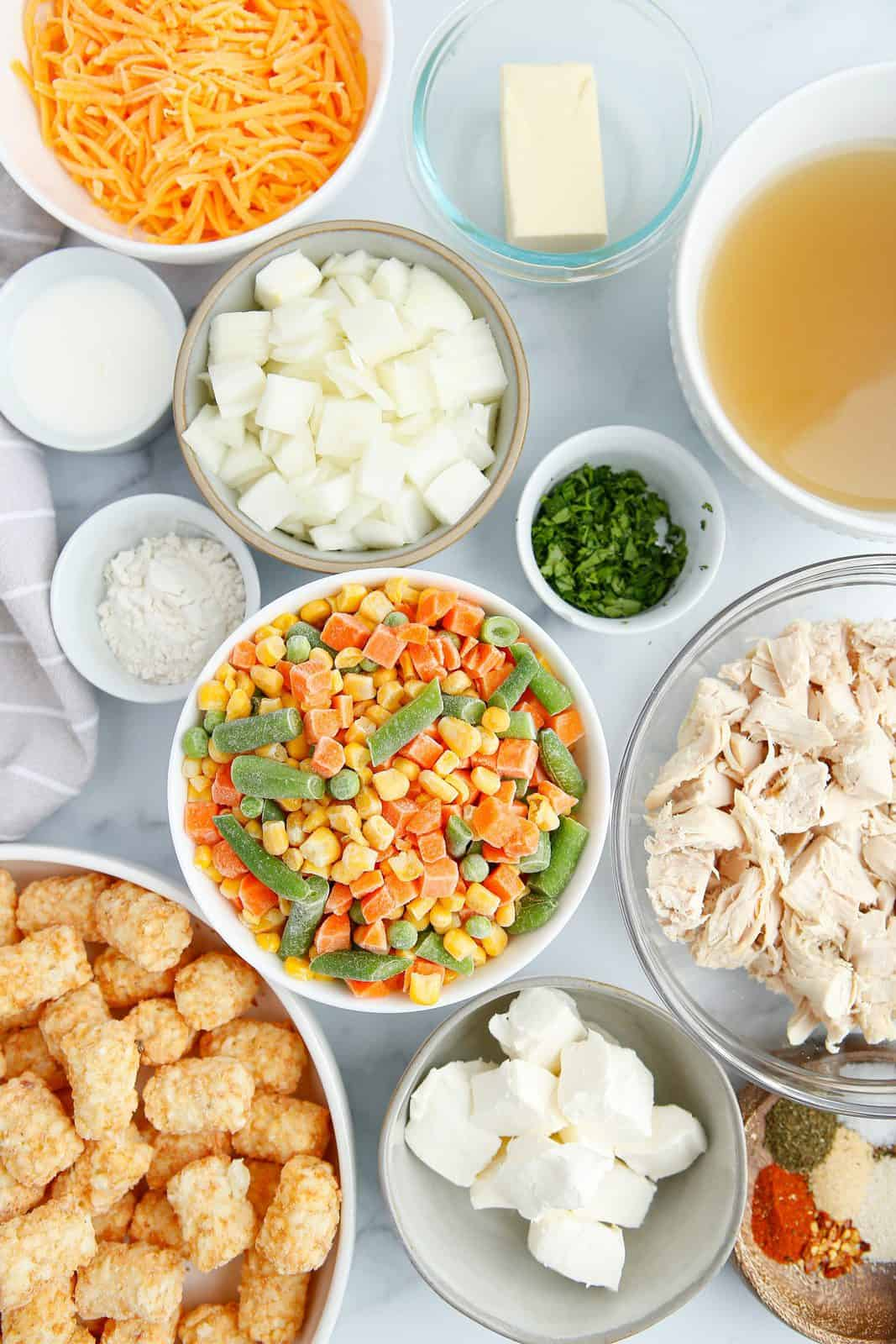 Ingredients needed: butter, rotisserie chicken, yellow onion, all-purpose flour, chicken stock, milk frozen mixed vegetables, cream cheese, paprika, onion powder, garlic powder, dried dill, dried thyme, salt, pepper, frozen tater tots, cheddar cheese and parsley.