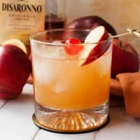 Square image of Apple Cider Amaretto Sour in glass with cherry and apple slice.