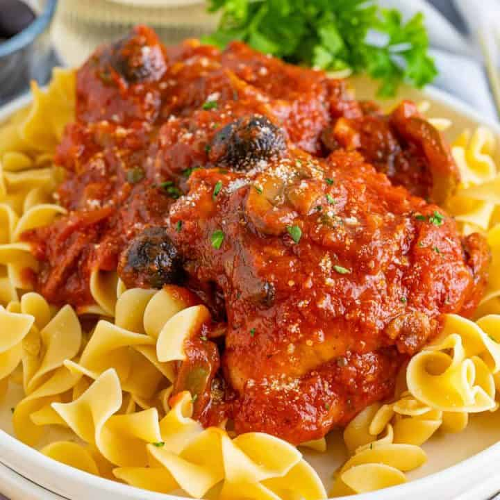 Square image of finished Chicken Cacciatore over noodles on white plate.