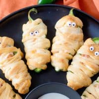 Square image close up of Halloween Mummy Jalapeno Poppers on black plate.