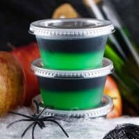 Square image of two stacked Halloween Poison Apple Jell-O Shots with fake spider and web.