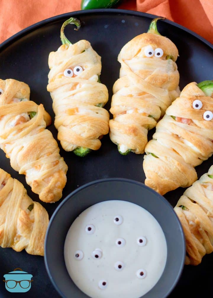 Halloween Mummy Jalapeno Poppers on black plate with dipping sauce.