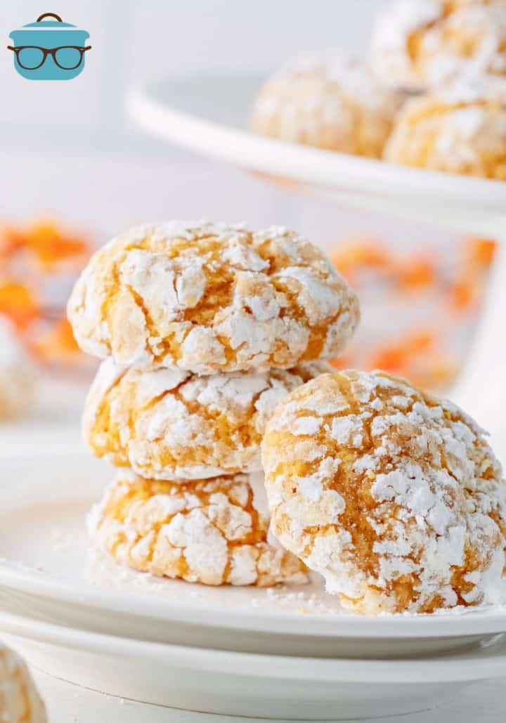 Three stacked Pumpkin Crinkle Cookies on white plate with another cookie leaning against others.