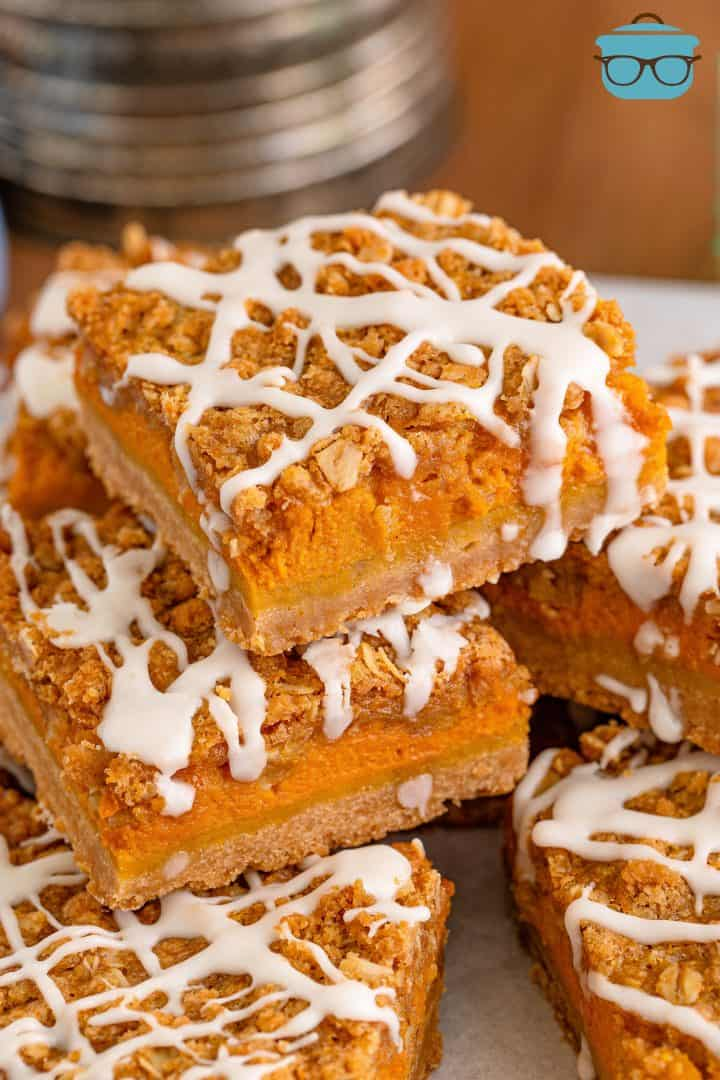 close up photo of a stack of pumpkin streusel bars on white parchment paper.